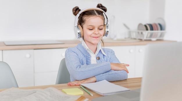 Bambina che studia con le cuffie Foto Gratuite