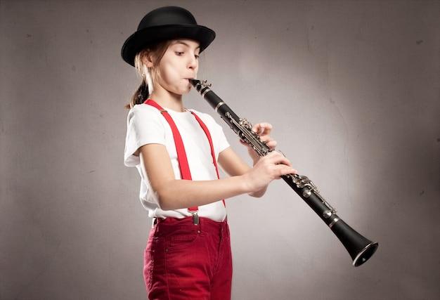 Bambina che suona il clarinetto Foto Premium