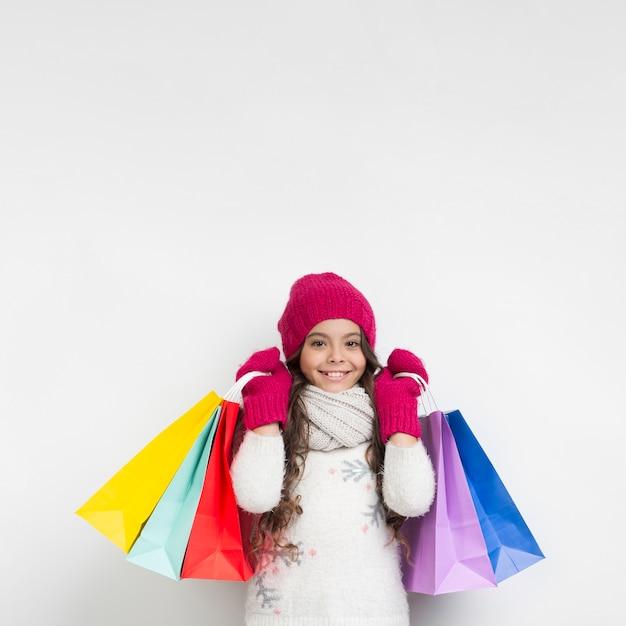 Bambina che tiene i sacchetti della spesa stagionali Foto Gratuite