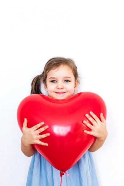 Bambina che tiene un bellissimo palloncino a forma di cuore rosso per un regalo per san valentino, innamorati, san valentino, famiglia e cuore Foto Premium