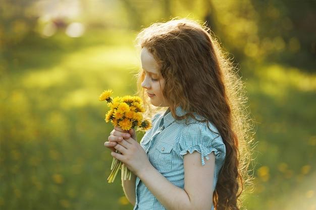 Bambina con bouquet di denti di leone gialli. Foto Premium