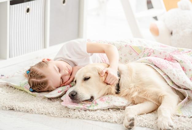 Bambina con cane sotto coperta Foto Premium