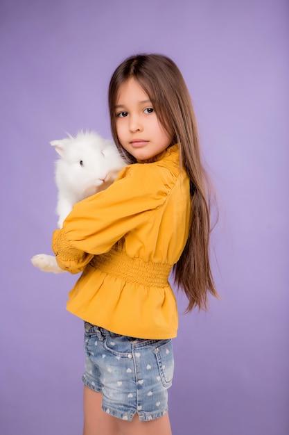 Bambina con coniglietto di pasqua su sfondo viola Foto Premium