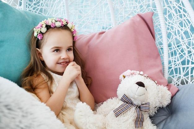Bambina con corona di fiori sui suoi capelli biondi scuri ...