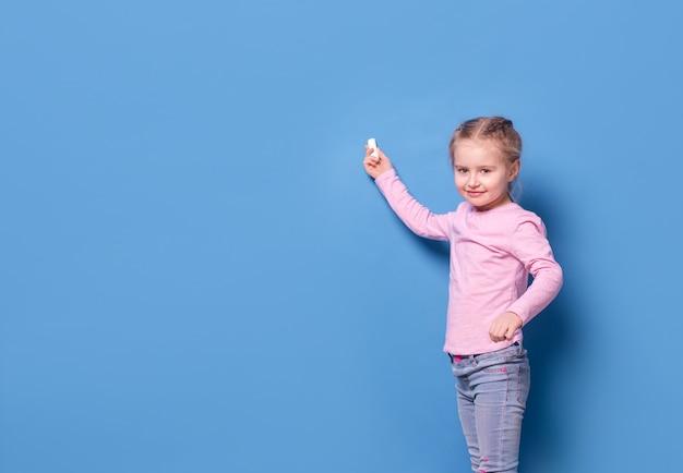 Bambina con gesso su sfondo blu Foto Premium