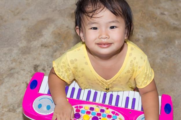 Bambina con giochi educativi giocattolo electone a casa, giochi da tavolo electone per l'apprendimento moderno dei bambini Foto Premium