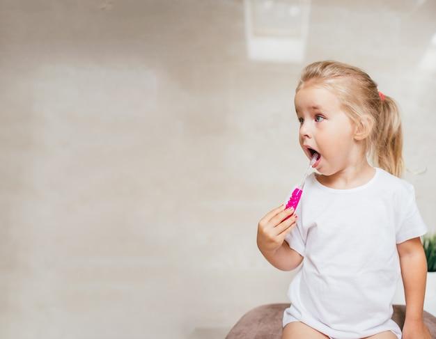 Bambina con i capelli biondi che pulizia dei denti con pennello e dentifricio in bagno. copyspace Foto Premium