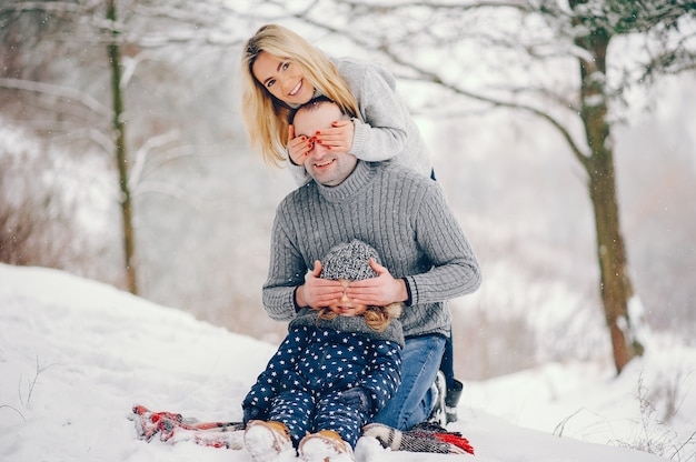 Bambina con i genitori seduti su una coperta in un parco d'inverno Foto Gratuite