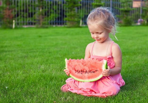 Bambina con il grande pezzo di anguria in mani su erba verde Foto Premium