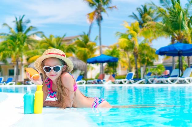 Bambina con la bottiglia di crema solare in piscina Foto Premium