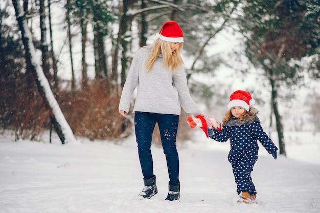 Bambina con la madre che gioca in un parco d'inverno Foto Gratuite