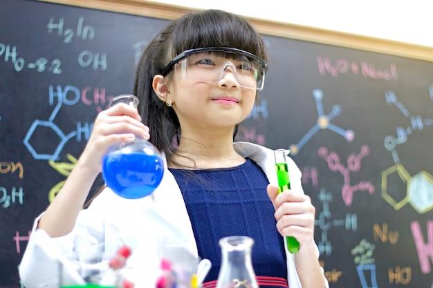 Bambina con la provetta che fa esperimento al laboratorio della scuola. scienza ed educazione. Foto Premium