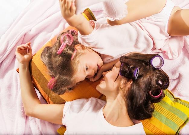 Bambina con sua madre che gioca a letto Foto Gratuite
