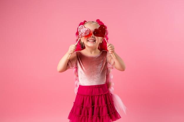 Bambina con trecce di kanekalon rosa detiene una lecca-lecca a forma di cuore su uno sfondo rosa Foto Premium