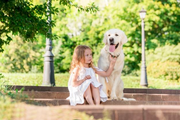Bambina con un grande cane bianco nel parco. una bella bambina di 5 anni in abito bianco abbraccia il suo cane preferito durante una passeggiata estiva. Foto Premium