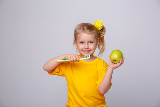 Bambina con uno spazzolino da denti, bambina con uno spazzolino da denti e una mela. Foto Premium