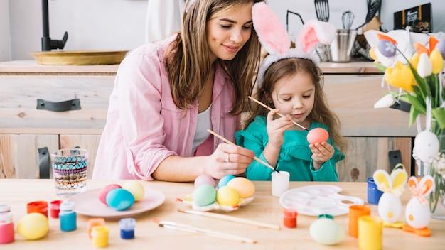 Bambina con uova di pittura madre per pasqua Foto Gratuite