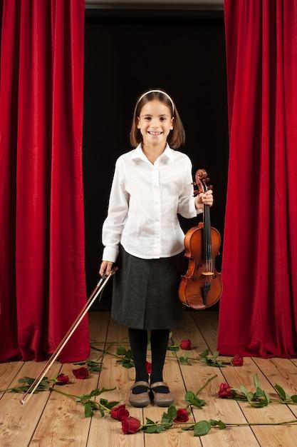 Bambina con violino in scena teatro Foto Premium