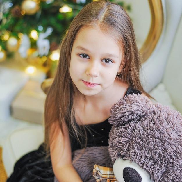 Bambina curiosa che sorride mentre aprendo i regali di natale. Foto Premium