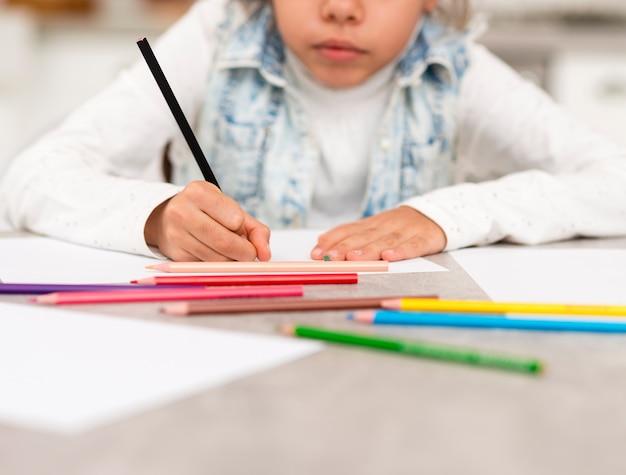 Bambina del primo piano che colora a casa Foto Gratuite