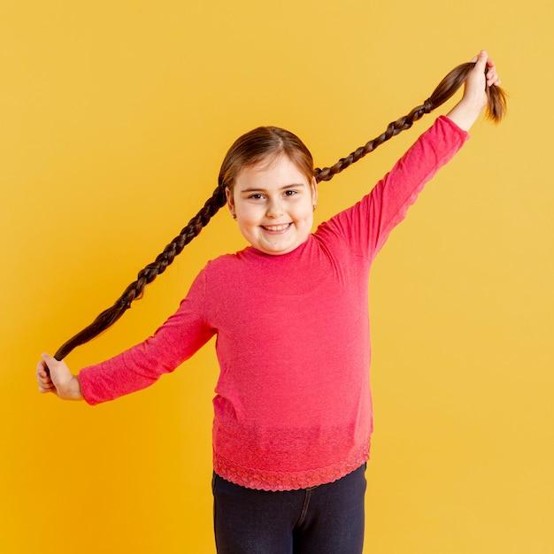 Bambina del ritratto che gioca con i suoi capelli Foto Gratuite