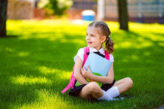Bambina della scuola con lo zaino rosa che si siede sull'erba dopo le lezioni che guardano lateralmente, leggono il libro o studiano lezioni Foto Premium