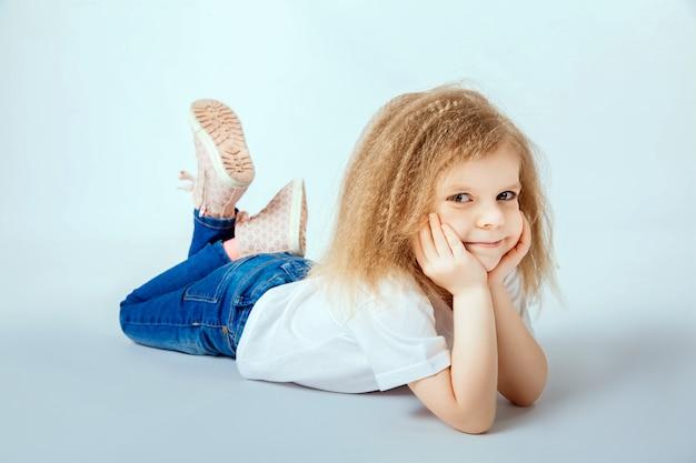 Bambina di 4 anni con i capelli ricci che indossa camicia bianca, blue jeans disteso sul pavimento, sorridendo e guardando, mani che tengono la testa Foto Premium