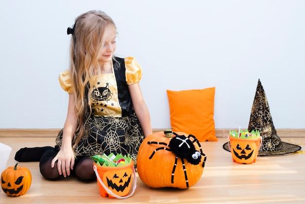 Bambina di vista frontale che si siede sul pavimento su halloween Foto Gratuite