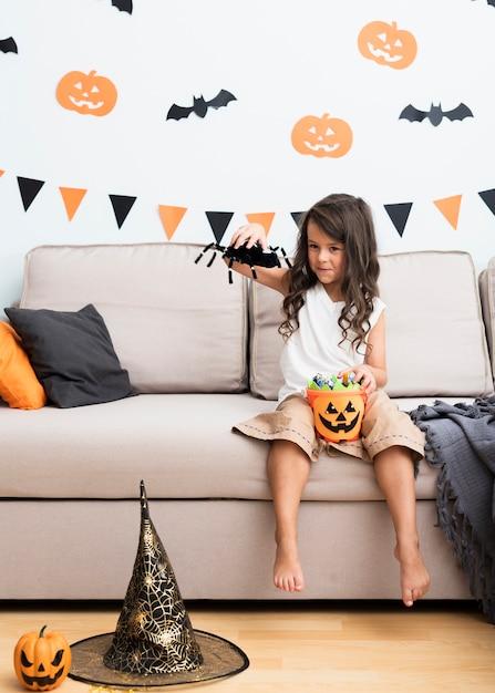 Bambina di vista frontale che si siede sullo strato su halloween Foto Gratuite