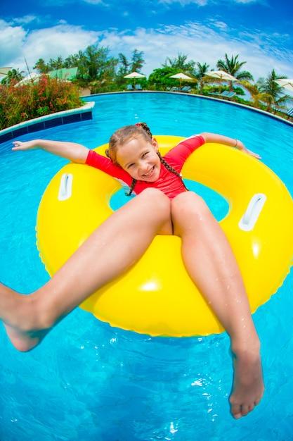 Bambina divertendosi nel cerchio di gomma gonfiabile alla piscina. vacanze estive in famiglia, bambino rilassarsi in piscina. Foto Premium