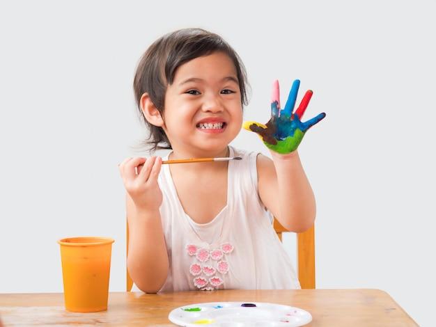 Bambina divertente con le mani dipinte su sfondo bianco. Foto Premium