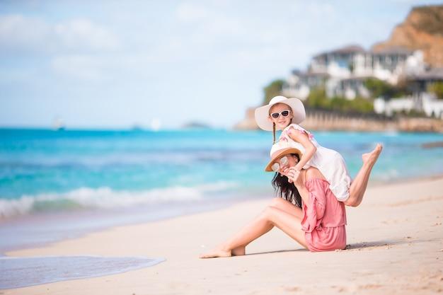 Bambina e giovane madre durante le vacanze al mare Foto Premium