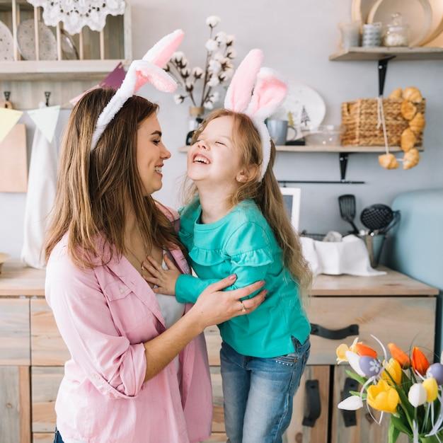 Bambina e madre nelle orecchie del coniglietto che ridono Foto Gratuite