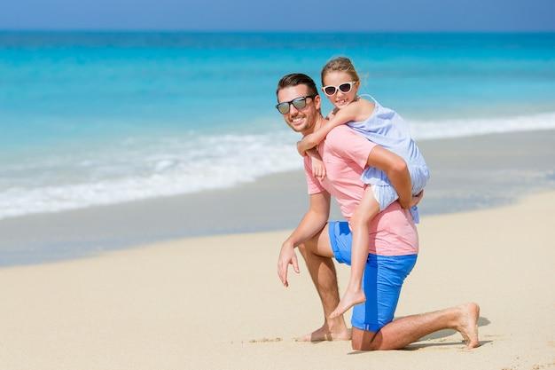 Bambina e papà felice divertendosi durante la vacanza della spiaggia Foto Premium