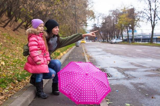 Bambina e sua madre che camminano con l'ombrello in una giornata piovosa Foto Premium