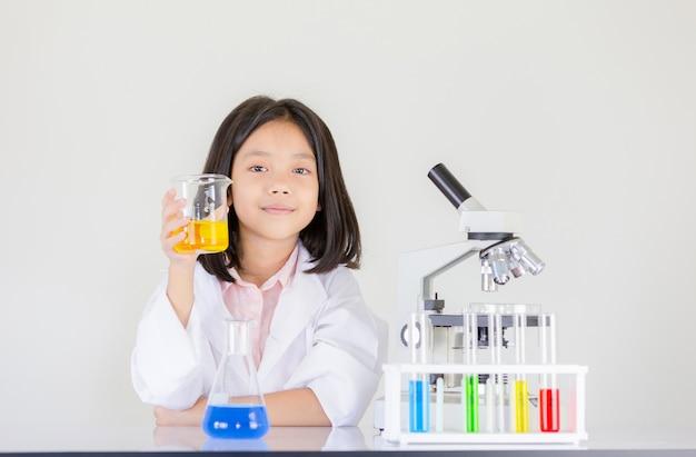 Bambina felice che gioca facendo esperimenti chimici in laboratorio Foto Premium