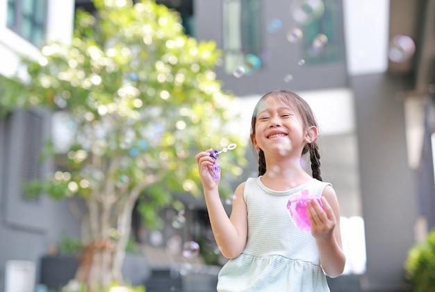 Bambina felice che gioca le bolle di sapone in giardino. Foto Premium