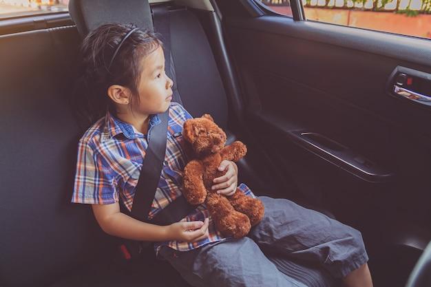 Bambina felice che indossa le cinture di sicurezza in auto Foto Premium