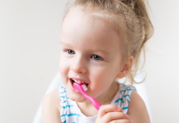 Bambina felice che pulisce i suoi denti, spazzolino da denti rosa, igiene dentale, stile di vita sano di concetto di notte di mattina Foto Premium