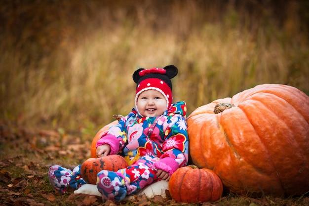 Bambina felice che si siede vicino alle zucche e che tiene un cestino con coniglio Foto Premium