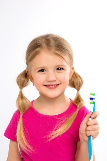 Bambina felice che sta con lo spazzolino da denti isolato su bianco. Foto Premium