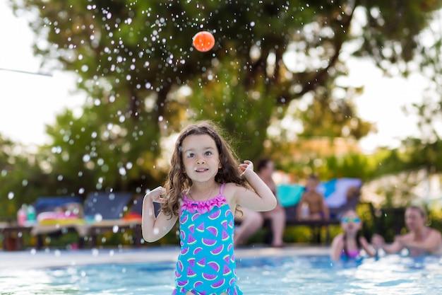 Bambina felice con i suoi capelli in giù in un costume da bagno luminoso che gioca palla nello stagno un giorno di estate soleggiato Foto Premium