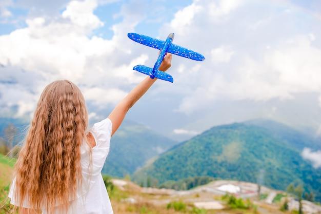 Bambina felice con l'aeroplano giocattolo nelle mani in montagna Foto Premium