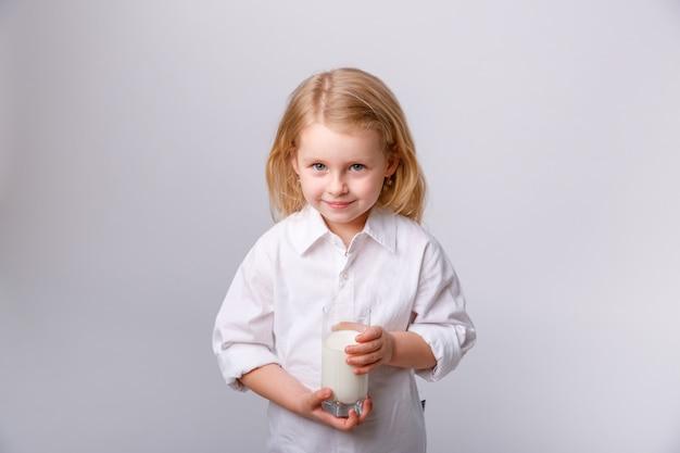 Bambina felice con un bicchiere di latte Foto Premium