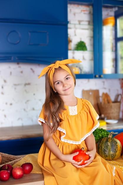Bambina felice in vestito giallo nella decorazione di autunno con le zucche in cucina, festa di halloween. raccolta. sana alimentazione, vegetarismo, vitamine, verdure. Foto Premium
