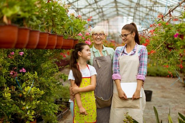 Bambina, giovane donna e donna senior che stanno nel giardino floreale Foto Premium