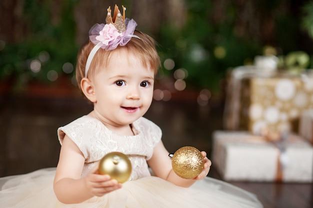 Bambina graziosa in vestito bianco che gioca e che è felice circa le luci di natale Foto Premium