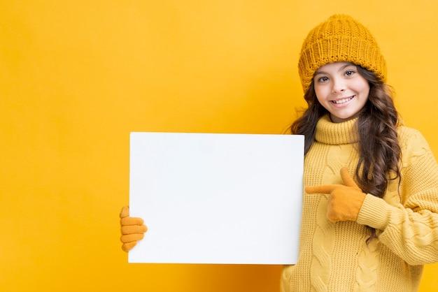 Bambina in abiti invernali tenendo lo strato di carta Foto Gratuite