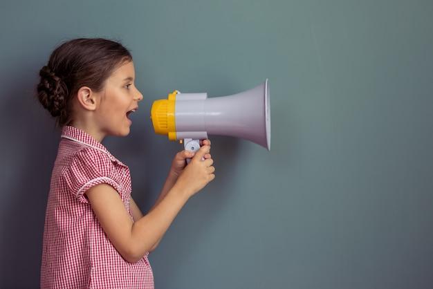 Bambina in abito carino urlando in un altoparlante Foto Premium
