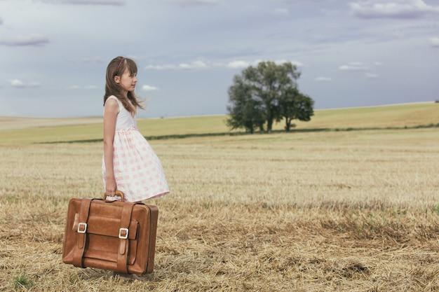 Bambina in abito classico con valigia da viaggio Foto Premium
